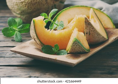 Fresh sweet orange melon on the wooden table, selective focus and toned image