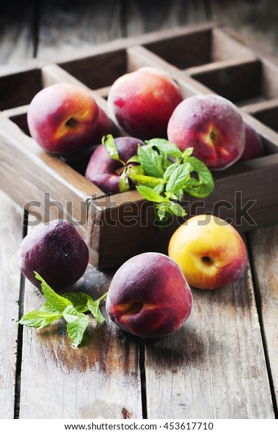 Fresh sweet peaches with mint, selective focus