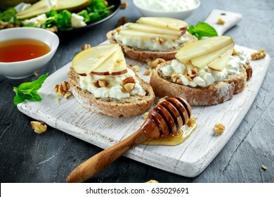 Fresh sweet Pears salad and bruschetta with cottage cheese, walnut on white board.