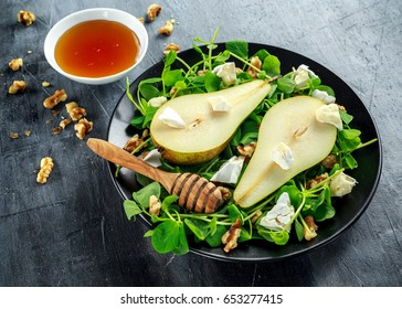 Fresh sweet Pears salad with walnuts, honey and white soft cheese on black plate