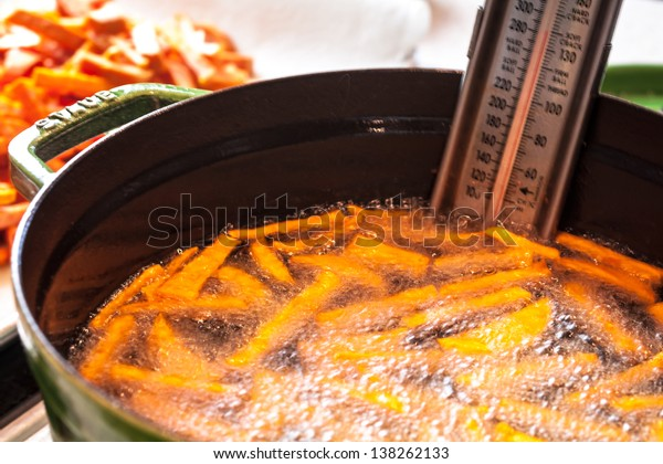 Fresh sweet potato french fried cooking in pot of hot vegetable oil