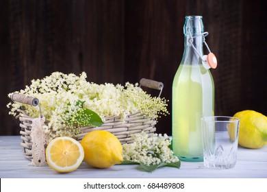 Fresh syrup from nigra sambucus with yellow lemons in glass bottle