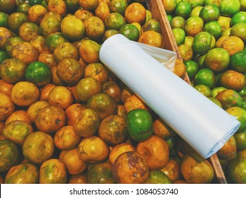 Fresh tangerine orange in modern trade supermarket. Mixed with orange and green colors. Plastic bag roll on top of oranges. Fruits have not perfect skin.