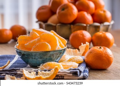 Fresh tangerine and segments on a blue tablecloth.