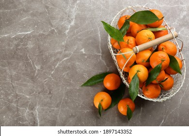 Fresh tangerines with green leaves on grey table, flat lay. Space for text