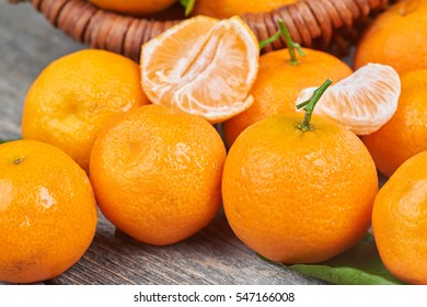 Fresh tangerines with leaves on a wooden table