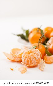 Fresh tangerines with leaves and peeled tangerines, sliced with peel. The beneficial properties of mandarins for health.