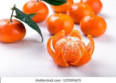 Fresh tangerines on a white background. Juicy mandarins with green leaves