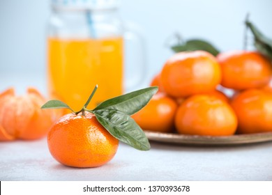 Fresh tangerines on a white background with glass jar. Juicy mandarins with green leaves.