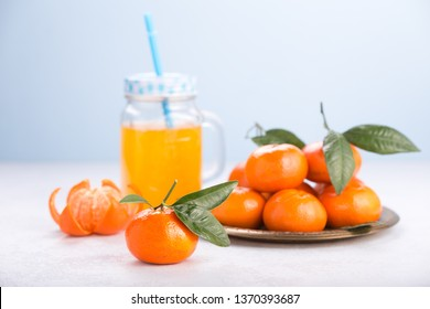 Fresh tangerines on a white table. Juicy mandarins with green leaves. Glass mug with handle.