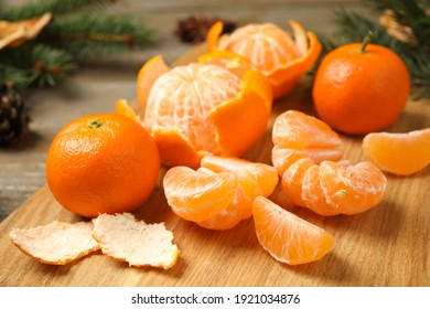 Fresh tangerines on wooden board, closeup. Christmas atmosphere