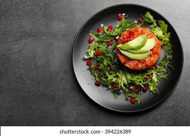Fresh tartar with salmon, avocado and arugula on black plate