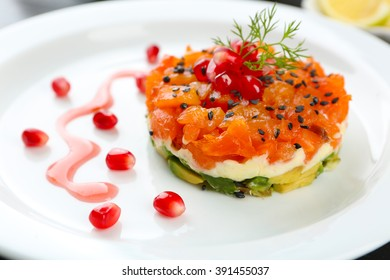 Fresh tartar with salmon and avocado and pomegranate seeds on white plate, close up
