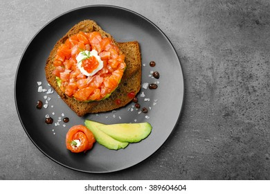Fresh tartar with salmon, avocado, red caviar and black bread on plate