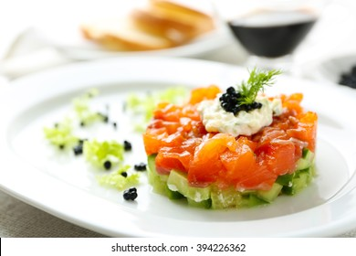 Fresh tartar with salmon, cucumber and black caviar on white plate, close up