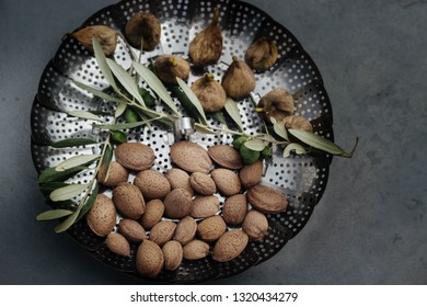 fresh, tasty almonds in shell and olive branches with olives fruits on a tray
