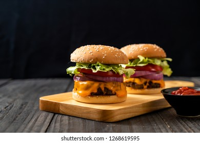 fresh tasty beef burger with cheese and ketchup on wood background
