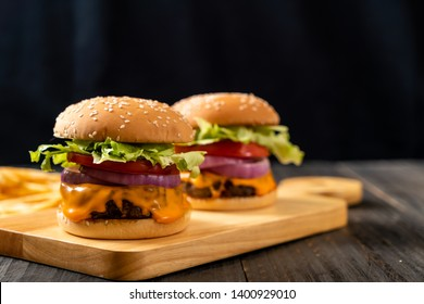 fresh tasty beef burger with cheese and french fries on wood background