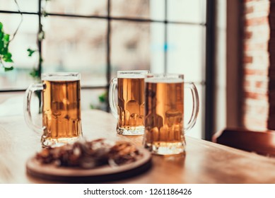 Fresh and tasty beverage. Close up of three mugs of beer on table at pub