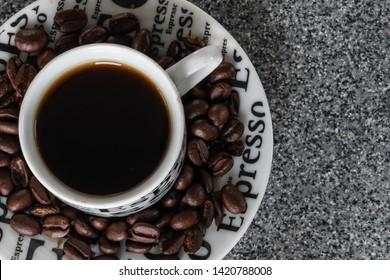 Fresh tasty black espresso cup of hot coffee with coffee beans on dark background