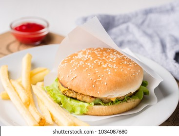 Fresh tasty burger and french fries served on white plate. Delicious burger with beef, tomato, cheese and lettuce served on paper on a wooden table. Street fast food