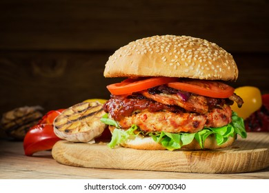 Fresh tasty burger. Hamburger close-up, sesame buns with succulent beef patty, grilled onions, bacon, tomato and fresh salad served on rustic wooden board. Homemade hamburger with fresh vegetables