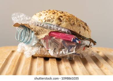 Fresh tasty burger with plastic waste and paper cardboard inside on wooden board. Recycled waste in our food concept.