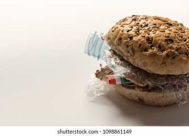 Fresh tasty burger with plastic waste and paper cardboard inside on white background. Recycled waste in our food concept.