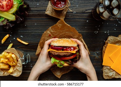 Fresh tasty burgers with french fries, sauce and drink on the wooden table top view.
