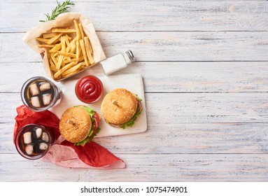 Fresh tasty burgers, two glasses with cola, french fries on white wooden background