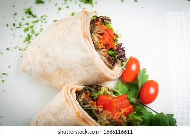 A fresh tasty California turkey wrap displayed on white platter with chopped parsley garnish