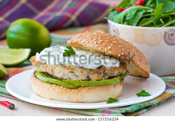 Fresh, tasty chicken burger in the Greek style with zucchini and yogurt cucumber sauce tzatziki, lime, salad