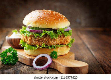 Fresh tasty chicken burger on wood table.