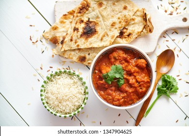Fresh and tasty Chicken tikka masala served in ceramic bowl. Indian spicy curry dish. With rice and naan bread on sides. Close up. Flat lay.