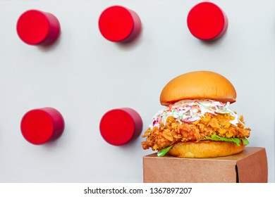 Fresh and tasty crispy chicken burger with cheese, coleslaw, lettuce, and sauce on the brown craft paper box and funky background. - Image