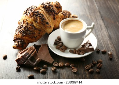 Fresh and tasty croissants with chocolate and cup of coffee on wooden background