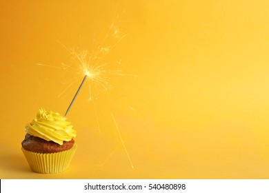 Fresh tasty cupcake with sparkler on yellow background