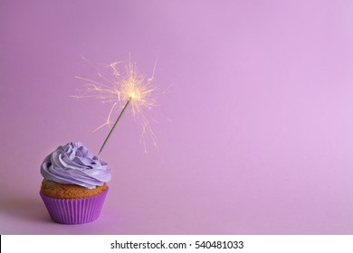 Fresh tasty cupcake with sparkler on lilac background