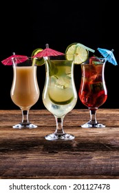 Fresh tasty drinks on black background with fruits