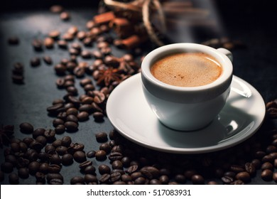 Fresh tasty espresso cup of hot coffee with coffee beans on dark background