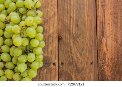 Fresh tasty grape with branch on wooden background