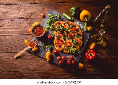 Fresh and tasty homemade pizza on wooden table with ingredients