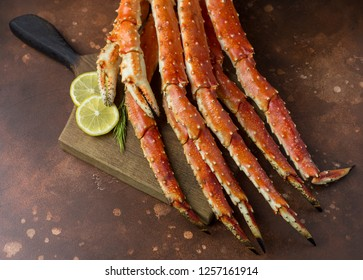 Fresh tasty king kamchatka crab's claw with lemon slices and rosemary on wood board at brown background
