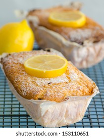 Fresh tasty lemon cake garnished with sliced lemon still wrapped in greaseproof paper cooling on a metal grid in the kitchen