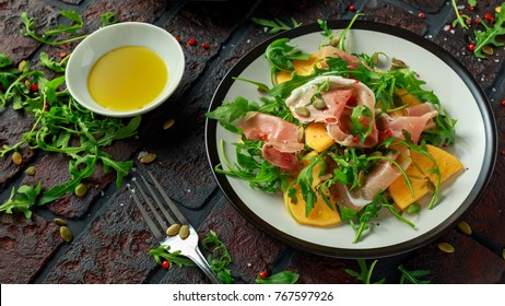 Fresh Tasty Persimmon salad with arugula, parma ham, olive oil, pumpkin seeds and herbs. autumn, winter healthy food