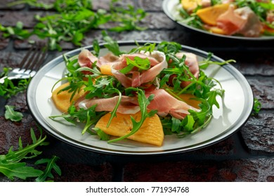 Fresh Tasty Persimmon salad with arugula, parma ham, olive oil and herbs. autumn, winter healthy food