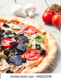 Fresh tasty pizza with asparagus, tomatoes, olives, mushrooms and herbs on a white wooden table. close up