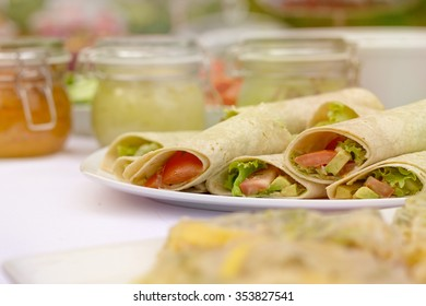Fresh and tasty sandwich wraps on the white plate and white tablecloth. Jars of jam in the background.