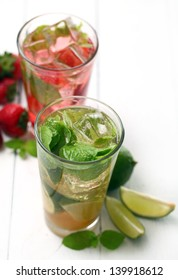 Fresh tasty strawberry and mint mojito on a white wooden table