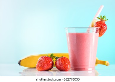 fresh tasty strawberry smoothie in glass cup with drinking straw on azure background. Strawberries and banana near the high ball